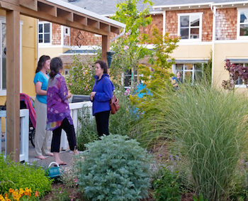three women talking to each other in a landscaped common area of a cohousing community