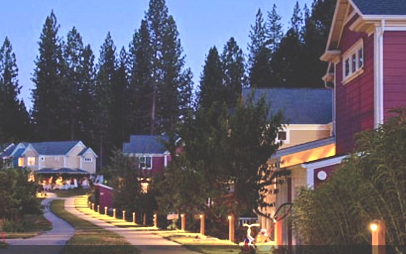 An image of a cohousing community at night with a lighted path linking small groups of row houses. People are outside in the far distance, and children's toys are in the foreground on the side of the paths.