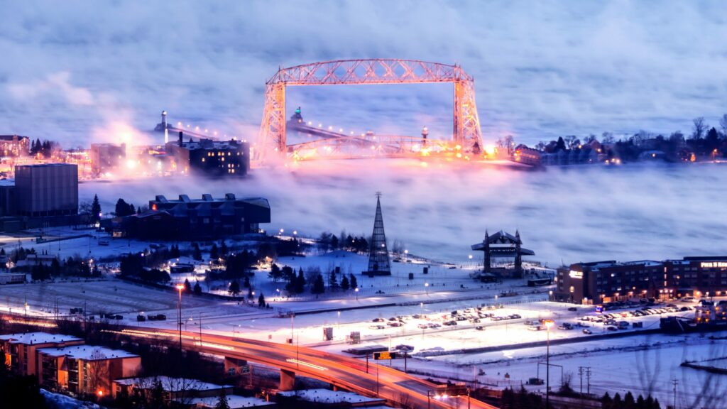 A wintry view of the Duluth, MN high bridge lighted during evening and viewed from the top of a near hill, with fog on Lake Superior, lights and traffic in the foreground.